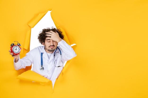 Vorderansicht männlicher arzt im medizinischen anzug, der uhren auf gelbem krankenhauseinkaufsmedizinzeitarztgesundheit hält