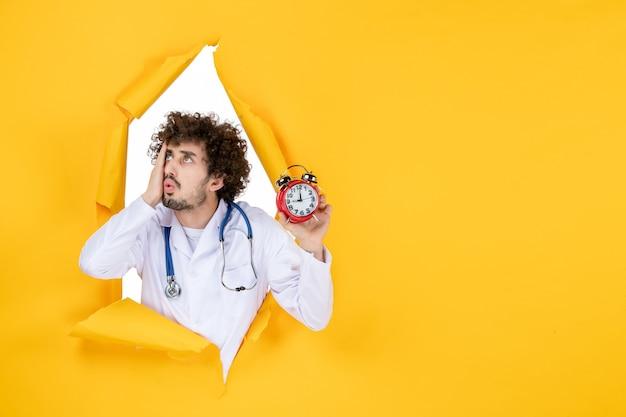 Vorderansicht männlicher arzt im medizinischen anzug, der uhren auf gelben gesundheitsfarben hält krankenhausarzt einkaufen medizinzeit