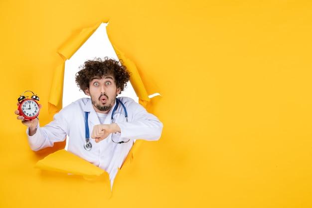 Vorderansicht männlicher arzt im medizinischen anzug, der uhren auf gelber farbe krankenhauseinkaufsmedizinzeitarztgesundheit hält