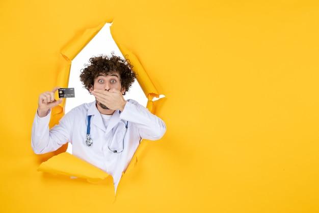 Vorderansicht männlicher arzt im medizinischen anzug mit bankkarte auf gelb zerrissener farbe medizin krankenhaus krankheit gesundheitsvirus mediziner