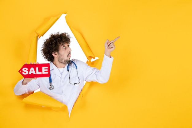 Vorderansicht männlicher arzt im medizinischen anzug mit roter verkaufsschrift auf gelber medizinfarbe