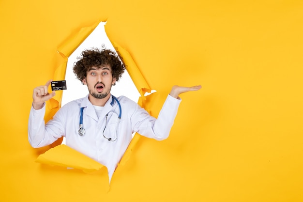 Vorderansicht männlicher arzt in medizinischem anzug, der eine bankkarte auf gelben zerrissenen farben hält