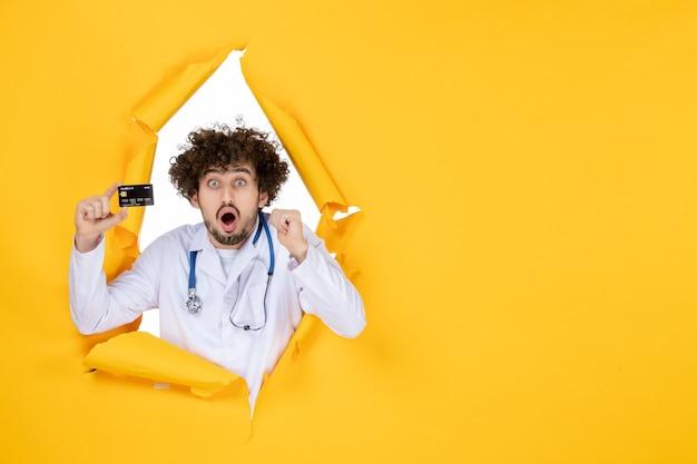 Vorderansicht männlicher arzt in medizinischem anzug, der eine bankkarte auf gelber, zerrissener farbe hält