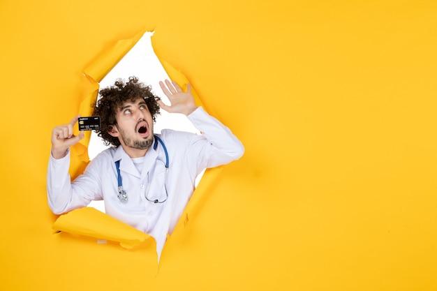 Vorderansicht männlicher arzt in medizinischem anzug mit bankkarte auf gelb zerrissener farbe medizinisches krankenhauskrankheits-gesundheitsvirus
