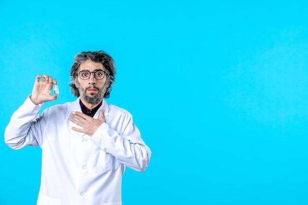 Vorderansicht männlicher arzt in medizinischer uniform, der eine kleine flasche auf einer blauen krankenhausvirus-farbwissenschaft hält