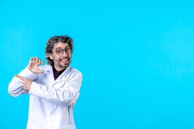 Vorderansicht männlicher arzt in medizinischer uniform, der kleine flasche auf dem blau hält