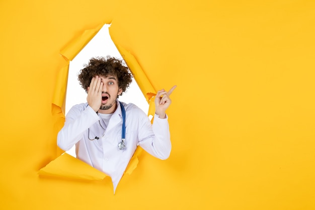 Vorderansicht männlicher arzt in weißem medizinischem anzug auf gelbem, zerrissenem gesundheitsmedizinvirus-farbkrankenhaus