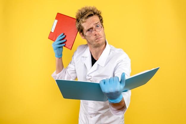 Vorderansicht männlicher arzt mit analysen auf gelbem hintergrund gesundheit covid human medic