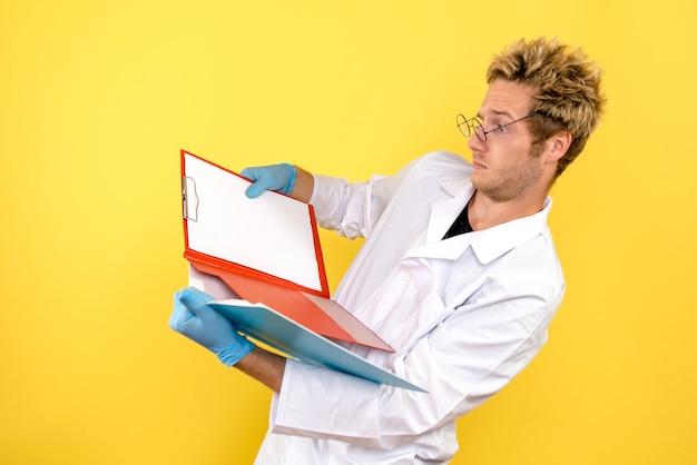 Vorderansicht männlicher arzt mit analysen auf gelbem hintergrund gesundheitsmediziner covid mensch