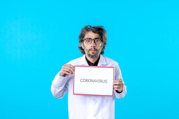 Vorderansicht männlicher arzt mit coronavirus-schriftzug auf blau