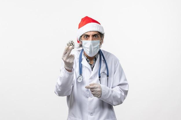 Vorderansicht männlicher arzt mit neujahrsbaumspielzeug auf weißem schreibtischvirusgesundheits-covid-
