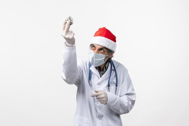 Vorderansicht männlicher arzt mit neujahrsbaumspielzeug auf weißer wandvirusgesundheit covid-