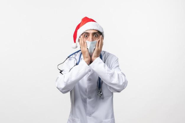 Vorderansicht männlicher arzt mit roter kappe und maske auf weißer wand neujahrskovidpandemie