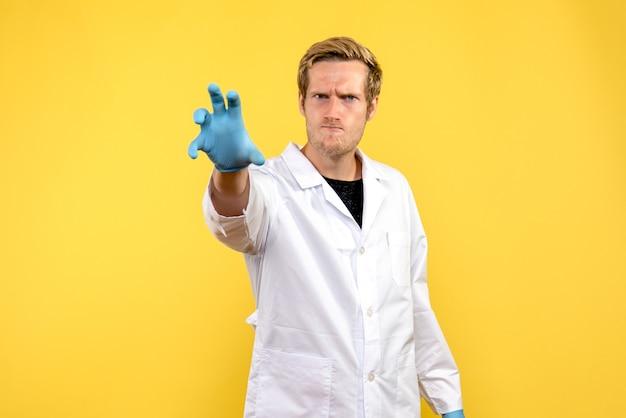 Vorderansicht männlicher arzt mit wütendem gesicht auf gelbem hintergrund gesundheitsmediziner covid-pandemie