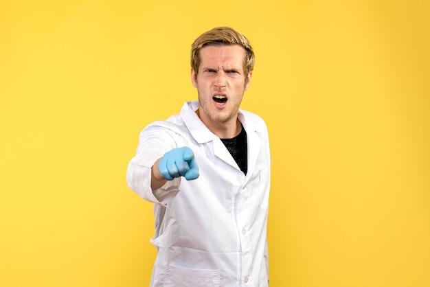 Vorderansicht männlicher arzt mit wütendem gesicht auf gelbem hintergrund medic pandemie covid mensch
