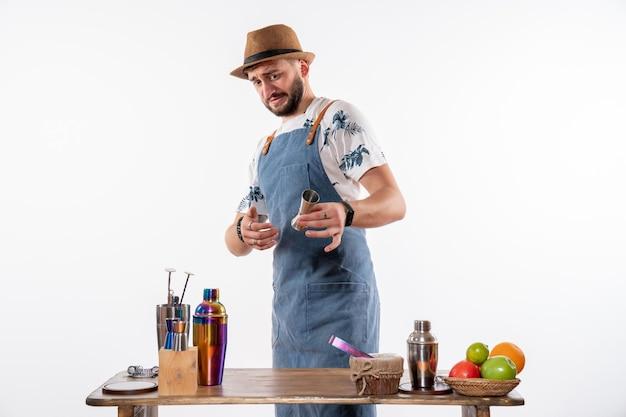 Vorderansicht männlicher barkeeper, der ein alkoholisches getränk auf der weißen wand nachtbar-alkohol-club-getränk-job macht