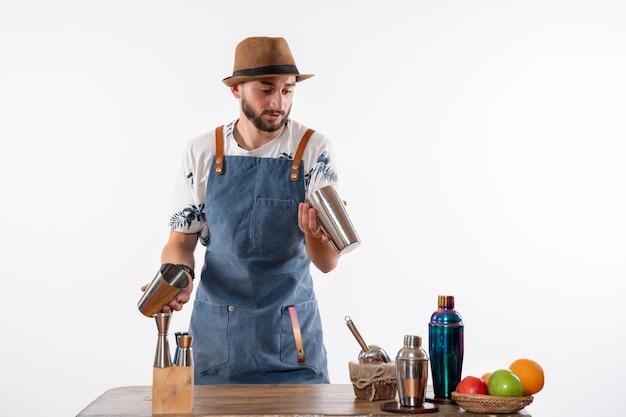 Vorderansicht männlicher barkeeper, der mit shakern auf weißem schreibtisch arbeitet, bar alkohol club nachtgetränkeservice