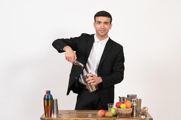 Vorderansicht männlicher barkeeper im anzug, der getränke auf der weißen wand macht nachtgetränkclub männlicher bartanz