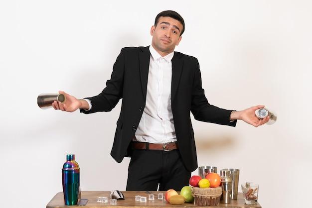 Vorderansicht männlicher barkeeper im anzug, der mit shakern arbeitet und einen drink auf dem weißen schreibtisch zubereiten kann