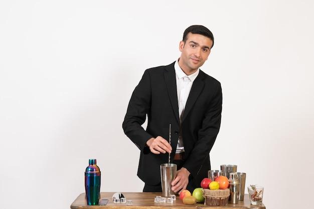 Vorderansicht männlicher barkeeper im anzug, der mit shakern arbeitet und getränke an der weißen wand zubereitet