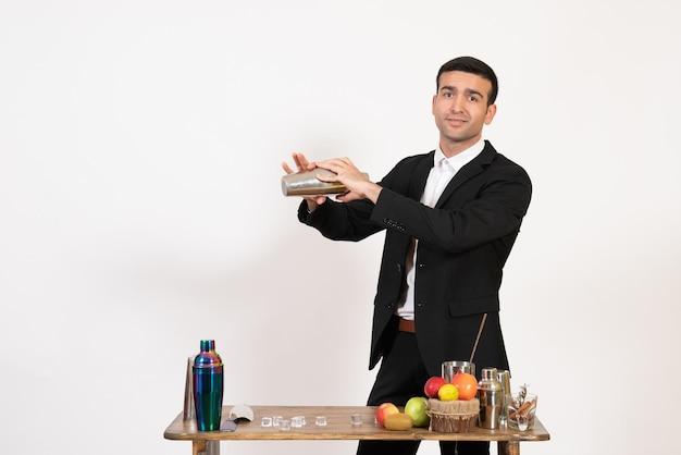 Vorderansicht männlicher barkeeper im anzug, der vor dem tisch mit shakern steht und getränke an der weißen wand zubereitet