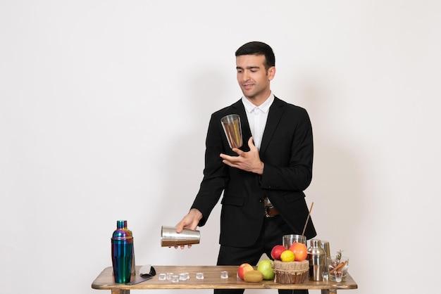Vorderansicht männlicher barkeeper im anzug, der vor dem tisch mit shakern steht und getränke auf weißem schreibtisch zubereitet männlicher bar-nachtclub-tanzgetränk