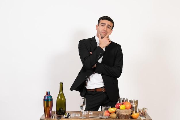 Vorderansicht männlicher barkeeper im klassischen anzug, der auf weißem wandclub steht und denkt, männliche nachtbar trinken alkohol