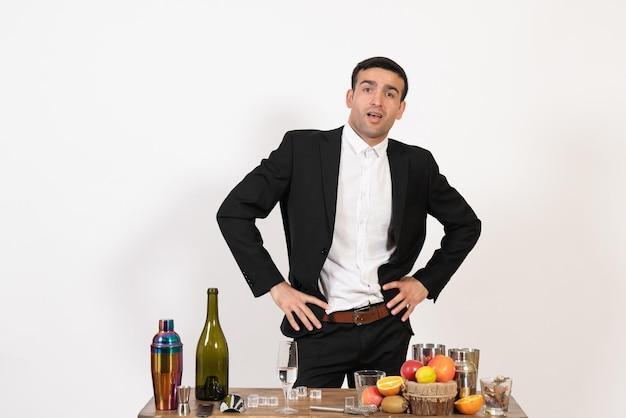 Vorderansicht männlicher barkeeper im klassischen anzug, der auf weißem wandclub steht und posiert, männliche nachtbar trinken alkohol