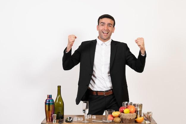 Vorderansicht männlicher barkeeper im klassischen anzug, der auf weißer wand nachtclub steht und sich freut, männliche bar trinken alkohol