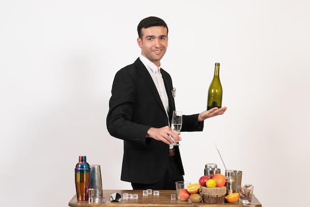 Vorderansicht männlicher barkeeper im klassischen anzug, der getränke auf der weißen wand macht nachtclub männliche bar trinkt alkohol