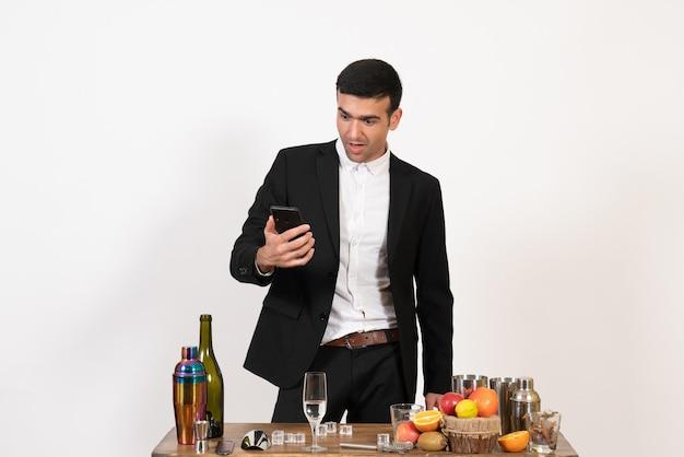 Vorderansicht männlicher barkeeper im klassischen anzug mit telefon an der weißen wand männlicher alkoholclub drink bar nacht