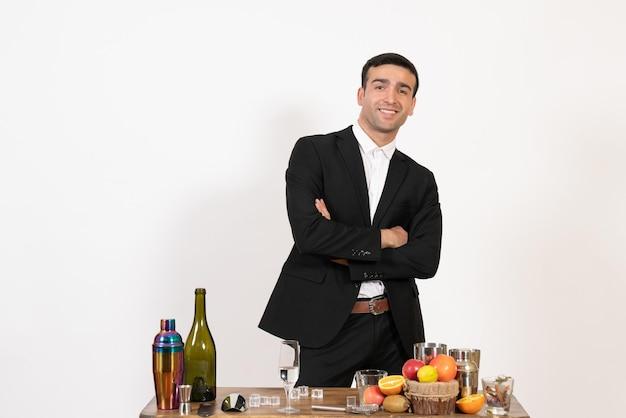 Vorderansicht männlicher barkeeper in klassischem anzug, der auf weißer wand steht und posiert nachtclub männliche bar trinken alkohol