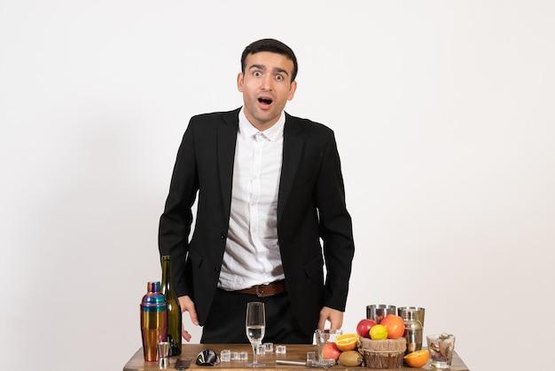 Vorderansicht männlicher barkeeper in klassischem anzug, der mit getränken auf weißer wand steht alkoholclubgetränk männliche nachtbar