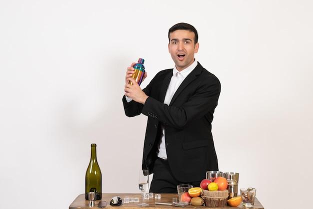 Vorderansicht männlicher barkeeper in klassischem anzug, der mit shaker arbeitet und getränke an der weißen wand zubereitet alkoholclubgetränk männliche nachtbar