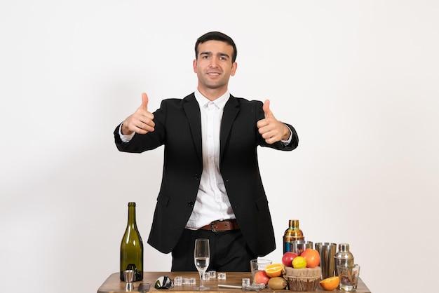 Vorderansicht männlicher barkeeper in klassischem anzug, der vor tisch mit getränken an der weißen wand steht männlicher alkoholclub drink bar nacht