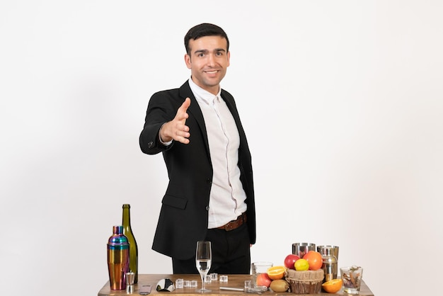 Vorderansicht männlicher barkeeper in klassischem anzug, der vor tisch mit getränken auf weißer wand steht alkoholclub trinken männliche nachtbar