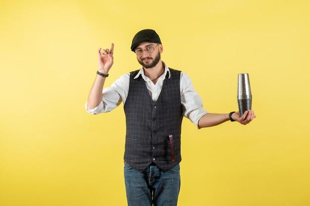 Vorderansicht männlicher barkeeper mit silbernem shaker an gelber wand trinken job club alkohol männliche bar nacht