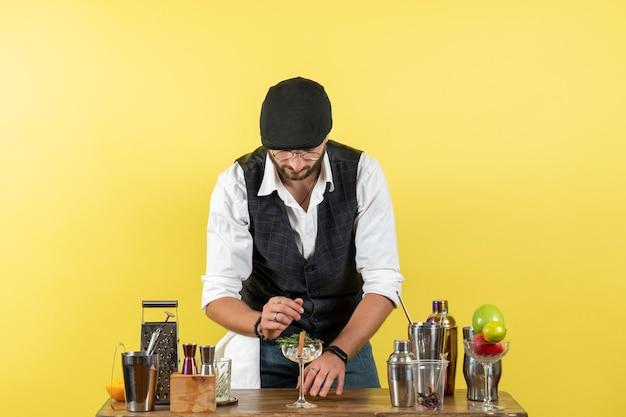 Vorderansicht männlicher barkeeper vor dem barschreibtisch, der getränke auf der gelben wandbar macht alkohol nachtjob obstgetränk club
