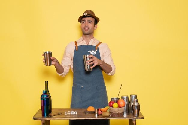 Vorderansicht männlicher barkeeper vor dem schreibtisch mit shakern und flaschen, die getränke an der gelben wand zubereiten, clubbar trinken nachtalkohol