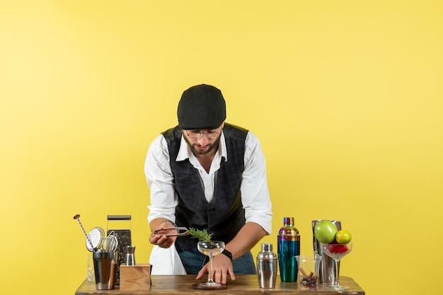 Vorderansicht männlicher barkeeper vor dem tisch mit shakern, die getränke auf der gelben bodenbar zubereiten, alkoholgetränk, nachtclubjugend