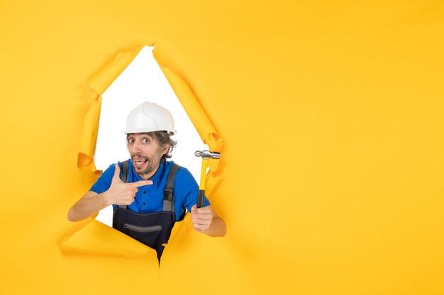 Vorderansicht männlicher baumeister in uniform mit hammer auf gelber wandfarbe arbeiter job architektur baumann