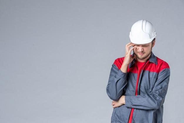 Vorderansicht männlicher baumeister in uniform und helm auf grauem hintergrund