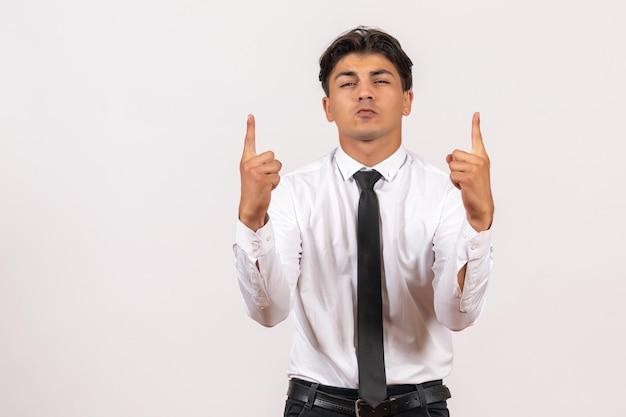 Vorderansicht männlicher büroangestellter, der auf weißer wand steht menschlicher büroarbeitsjob männlich