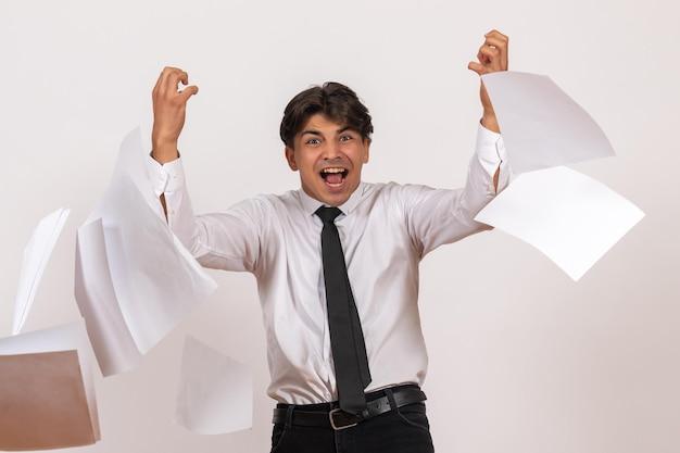 Vorderansicht männlicher büroangestellter, der dokumente auf weiße wand wirft, arbeitet menschlichen job männlich