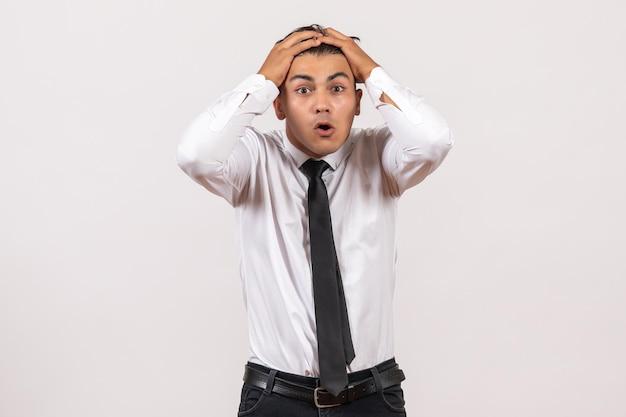Vorderansicht männlicher büroangestellter, der sich auf weiße wand büroarbeitsjob männlicher mensch aufgeregt fühlt