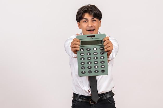 Vorderansicht männlicher büroangestellter, der taschenrechner auf weißem schreibtisch hält, arbeitet menschlichen job männlich