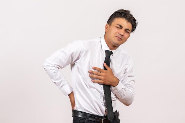 Vorderansicht männlicher büroangestellter mit rückenschmerzen auf weißer wand arbeiten männliches jobgeschäft