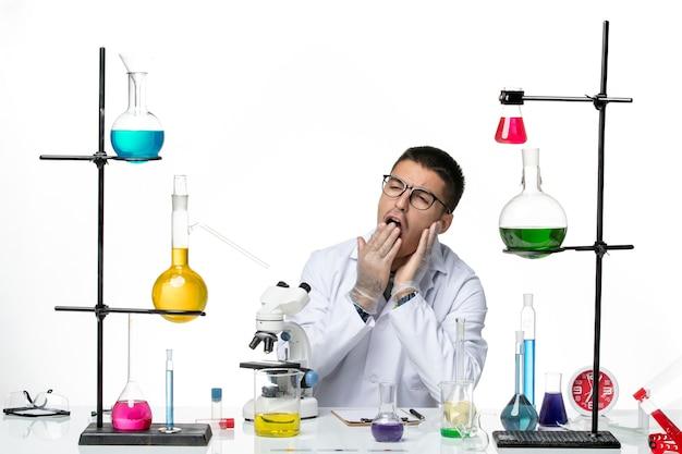 Vorderansicht männlicher chemiker im weißen medizinischen anzug sitzend mit lösungen, die auf weißem hintergrundviruslabor covid disease science gähnen