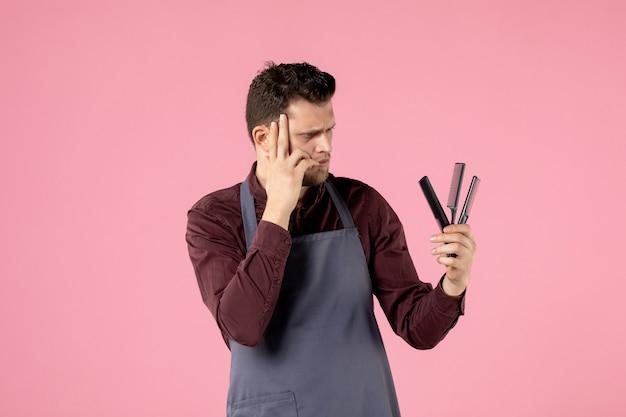 Vorderansicht männlicher friseur mit haarbürsten auf rosa hintergrund