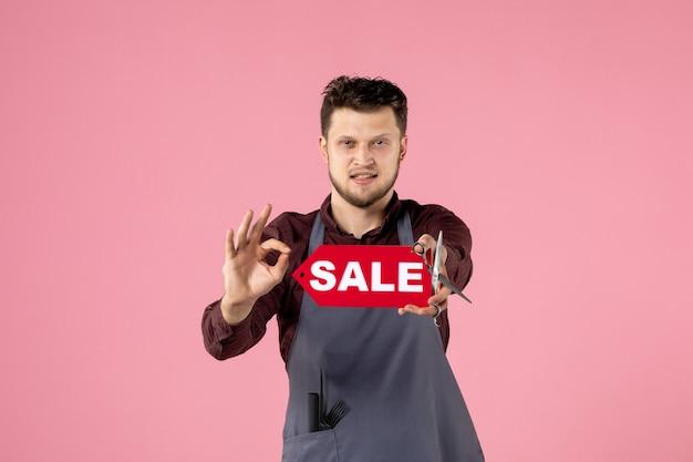 Vorderansicht männlicher friseur mit rotem verkaufsschild auf rosa hintergrund